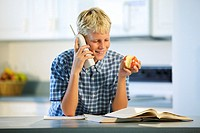 A teen boy eats an apple and talks on the phone instead of doing his homework