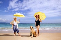 Portrait of two women at the beach, holding umbrellas and standing with their dog