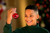 Portrait of a smiling boy holding up a  Christmas ornament