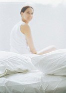 Woman sitting on bed, blurred