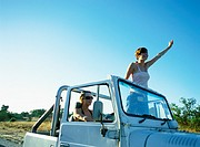 Two women in 4x4 vehicle, one standing up, waving