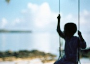 Silhouette of child sitting on swing, blurred