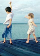 Two children standing on dock waving arms, blurred