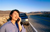Woman on cell phone while at the side of road
