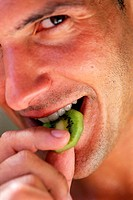 close-up of man eating a slice of kiwi fruit