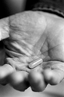 close-up of open hand holding a pill