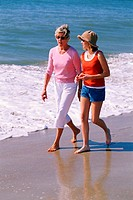 shot of mature adult female and young teenage girl walking in the sand talking at the beach