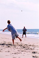 teenage boy and adult male throwing a baseball back and forth in the sand at the beach