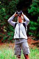 A woman hiker standing in tall grass looking through binoculars