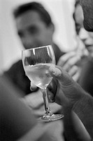Closeup of woman´s hand holding wine glass, people in background