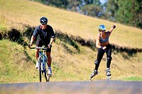 A male mountain bike riding beside a female inline skating on a paved mountainous road