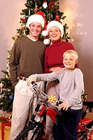 Portrait of family in front of Christmas tree