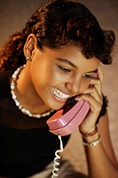 Portrait of a teenage girl smiling as she talks on the telephone
