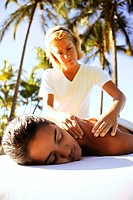 Close-up of a woman receiving a table massage in a tropical setting