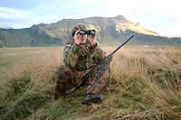 Hunter looks through his binoculars while sitting on a grassy knoll