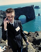 Man wearing suit and glasses, holding a mobilephone and sea and cliff behind him