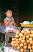 Young baby girl in a fruit market. Bali, Indonesia