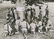 Soldiers crouching around a tree