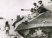 Soldiers in a tank regard a small child