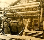Soldiers standing outside a log cabin
