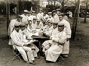 A group of soldiers dressed in white sitting at a table