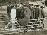 A group of soldiers looking at a wooden training horse