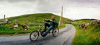 A man driving a  bicykle in a lonely road in Ireland