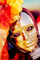 Large clear eyes looking through a gold facemask worn at the yearly carnival in Venice. Italy