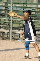 Black female retrieves softball during a practice session