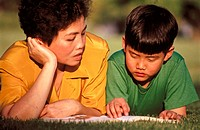 Asian mother and son reading