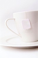 High key white tea cup and saucer on white background with teabag string over the side