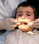 Dental check-up. Seven-year-old boy having his teeth checked by a dentist. The dentist is using an angled mirror to observe the condition of the teeth...