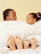Children´s feet. Four-year-old girl and her five-year-old brother sitting in bed with their feet sticking out from the duvet.