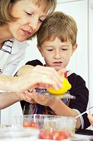 Preparing salad. 5-year-old boy helping his mother to grate a lemon into a salad.