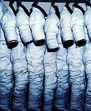 Space suits hanging in a row from hooks. These space suits, known as Extravehicular Mobility Units (EMUs), have been designed for use during shuttle m...
