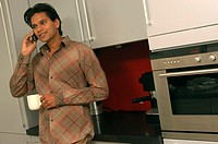 Young man using mobile in kitchen (thumbnail)