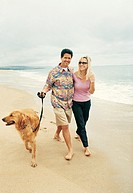 Couple Walking Dog on Beach at Waters Edge