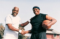 Two Elderly Men Shaking Hands on a Basketball Court