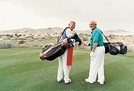 Rear View Portrait of Two Senior Men Standing on a Putting Green Carrying Golf Bags