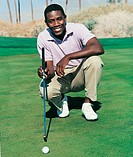 Golfer Crouching Down on a Putting Green