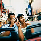 Young Tourist Couple Sightseeing on a Bus in New York, With the Man Taking a Photograph