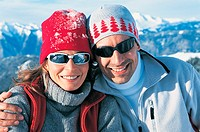 Portrait of a Smiling Couple in Warm Clothing and Shades on a Mountain