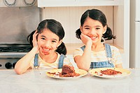 Portrait of Twin Sisters in a Kitchen, With Messy Chocolate Mouths and Half-eaten Chocolate Cake on Plates
