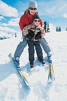 Portrait of a Mother and Her Young Son Standing on a Mountain Ski Slope With Their Skis