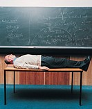 Tired Maths Lecturer Lying on a Table in a Classroom