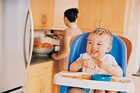 Messy Baby Sitting in a Highchair Eating Spaghetti and its Mother in the Background