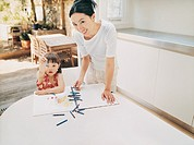 Mother Standing at a Kitchen Table by Her Daughter With Her Colouring In Book and Crayons