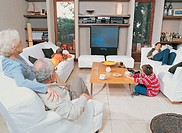 Grandparents Sittng in a Living Room With Their Grandchildren Watching TV