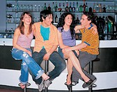 Two Smiling, Young Couples Sitting on Stools at the Bar