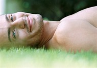 Smiling Young Man Lying Naked in the Grass